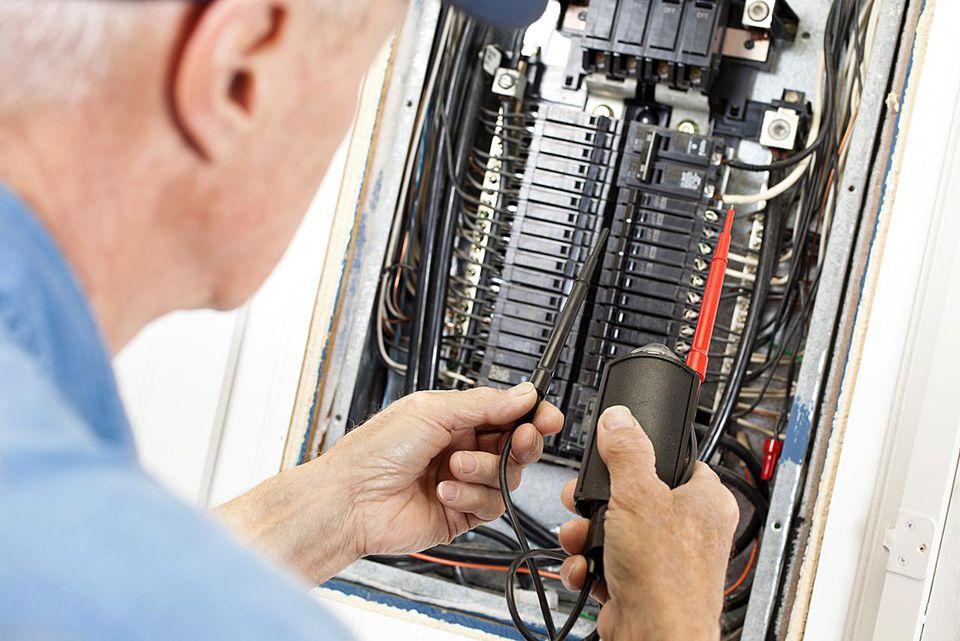 Electrician doing electrical work in breaker box