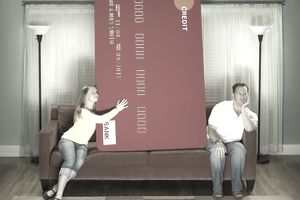 A couple sits with an oversize credit card