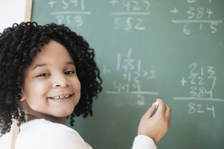 African American student writing on chalkboard in classroom