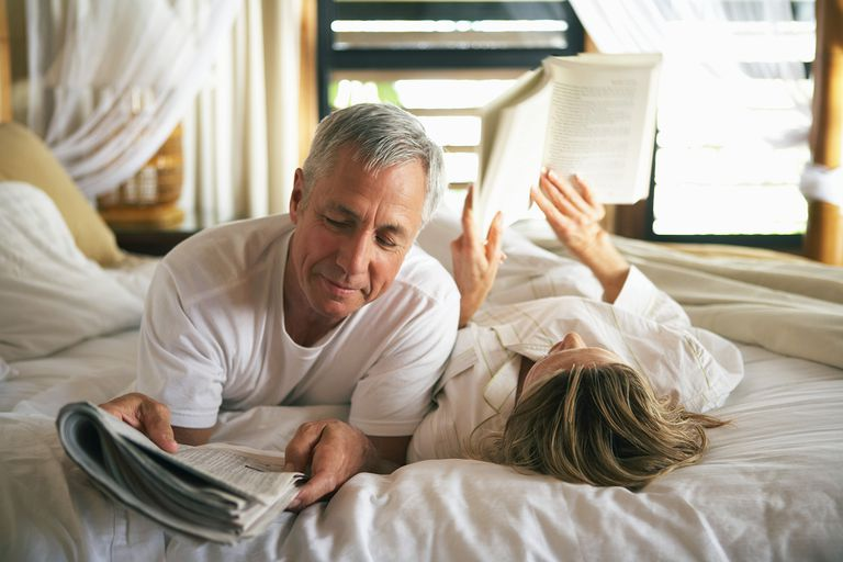 Senior couple reading in bed, close-up.
