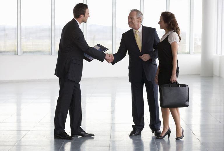 Letting agent showing business people around empty office