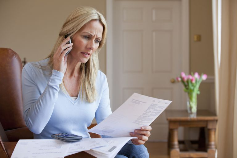concerned woman on phone looking at bills