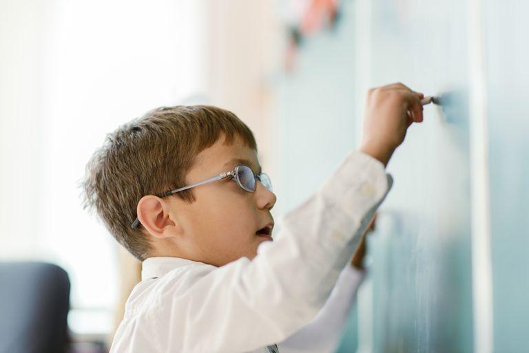 Schoolboy writing on chalk board