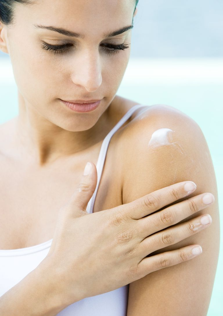 Woman applying topical corticosteroids to shoulder