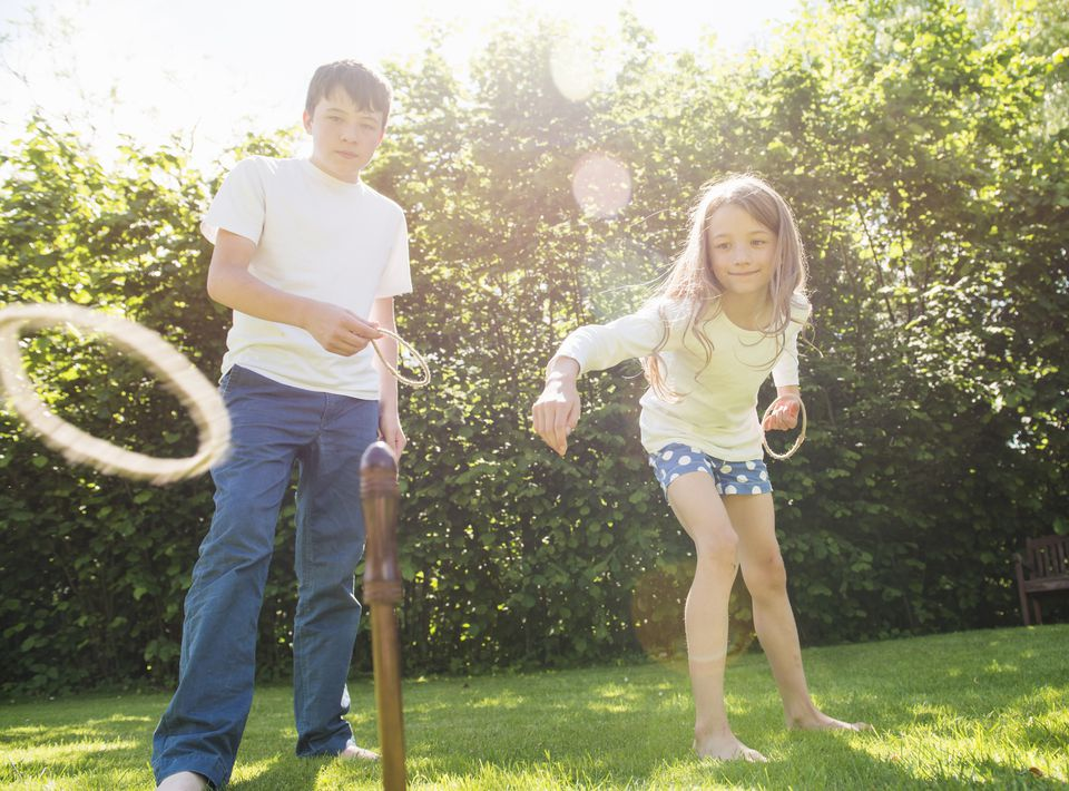 Brother and sister playing hoopla in garden