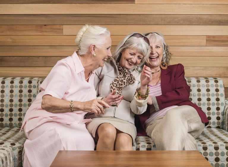 Senior women friends laughing on sofa