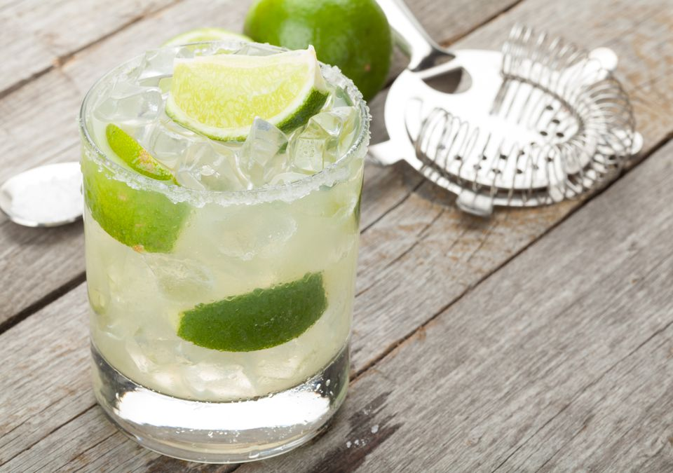 Margarita with a salted rim on a wooden table, with bar tools and a lime in the background.