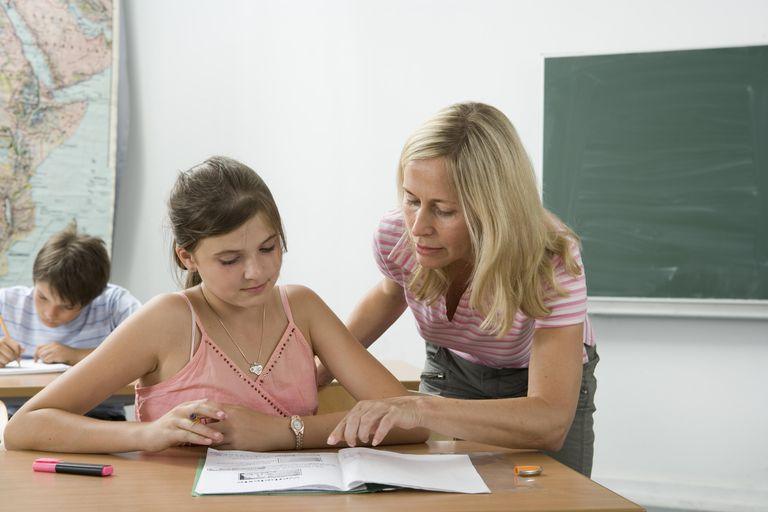 A teacher helping a student in a classroom.