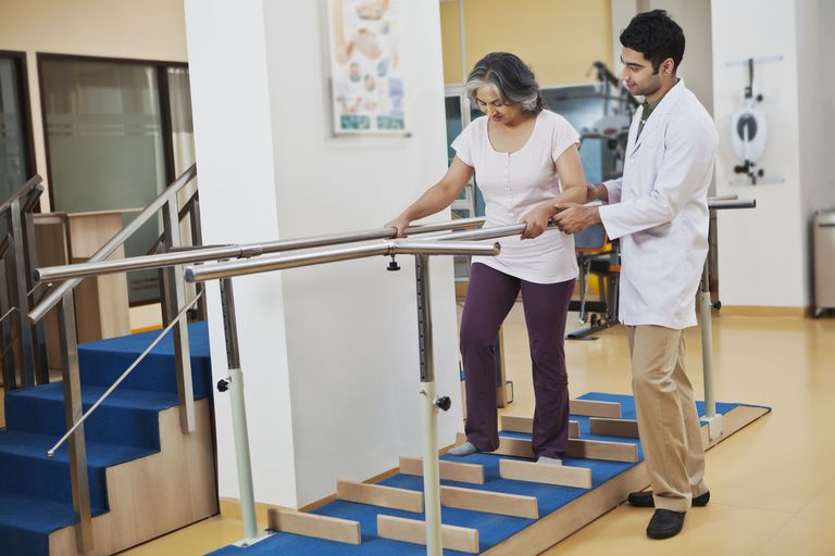 Physical therapist helping woman do a walking exercise