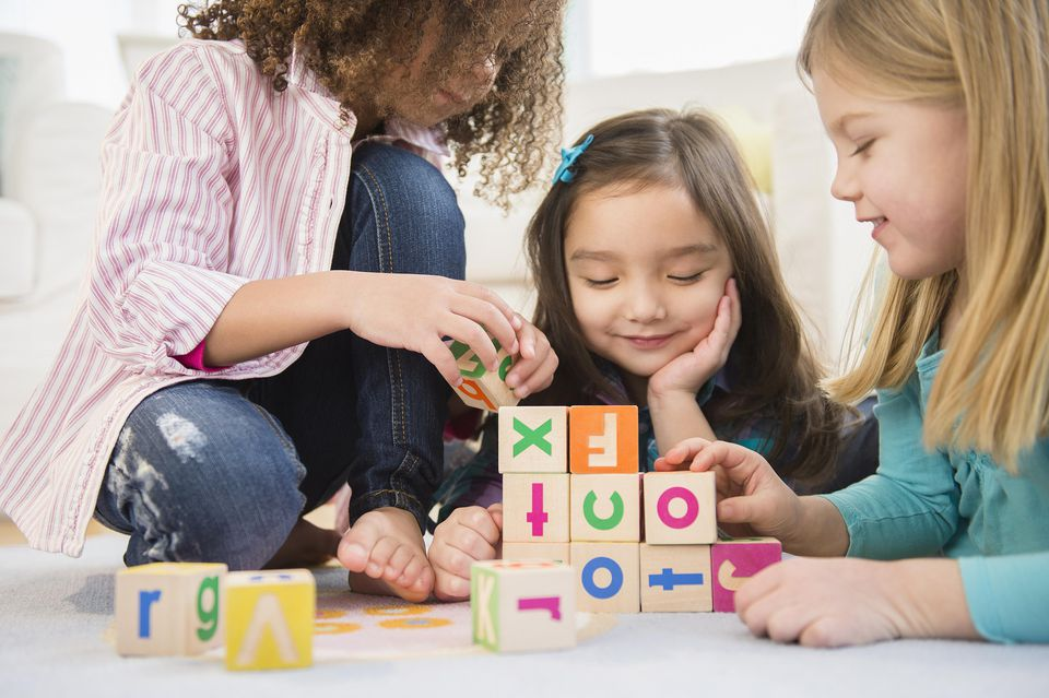 young girls building with wooden alphabet blocks