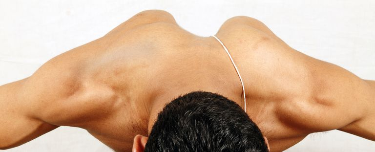 photo of man lying on stomach with shoulder blades protruding