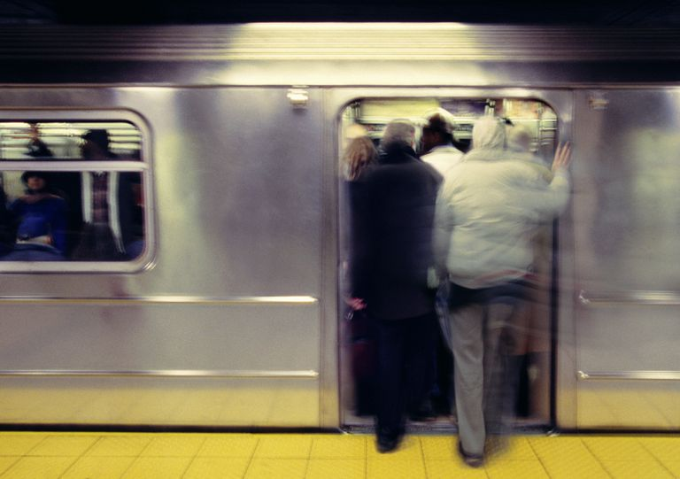 Passengers stepping in to crowded train, rear view (blurred motion)