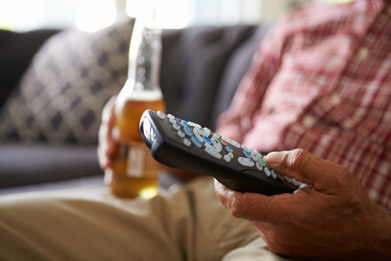 Man Sitting On Sofa Holding TV Remote And Bottle Of