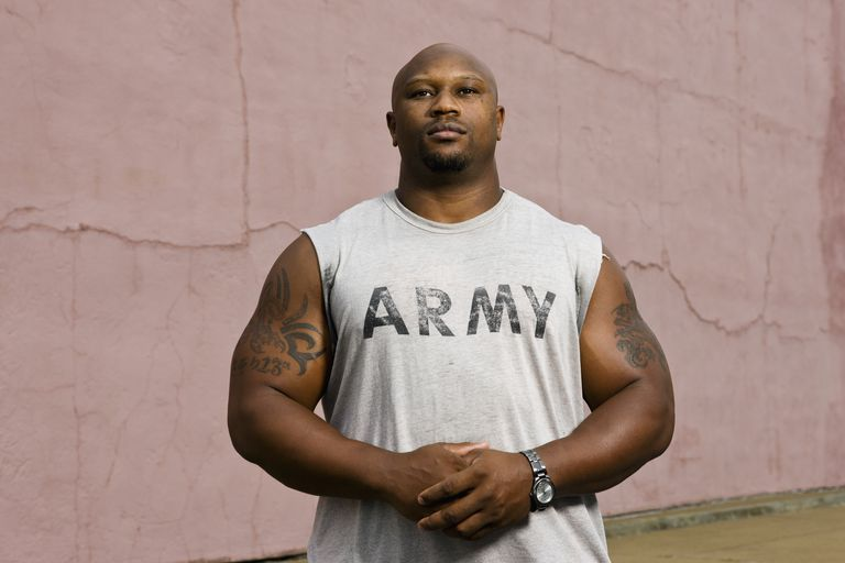 man with tattoos in army shirt