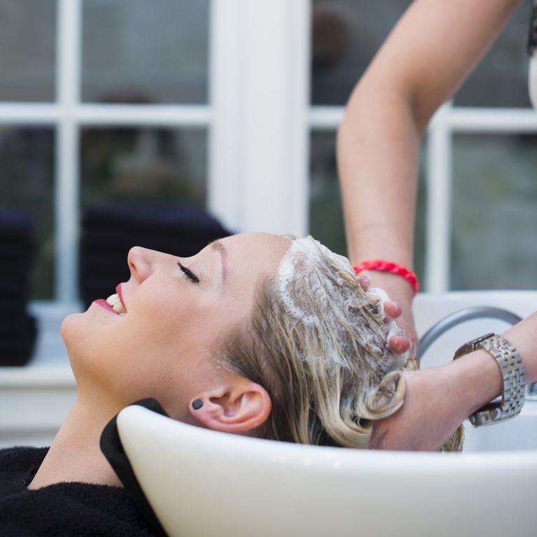 Woman having hair shampooed in salon
