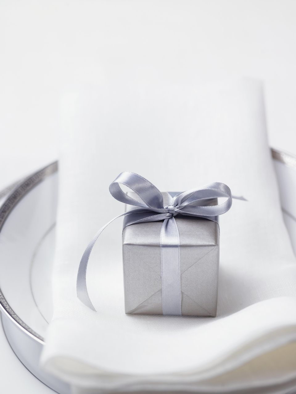 Silver miniature decorative gift box on napkin, close-up