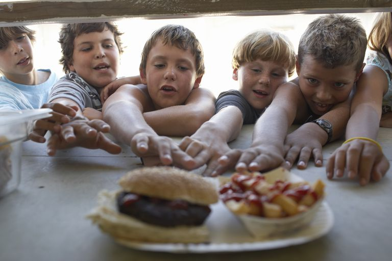Children (6-10) at fastfood vendor's window, reaching for plate