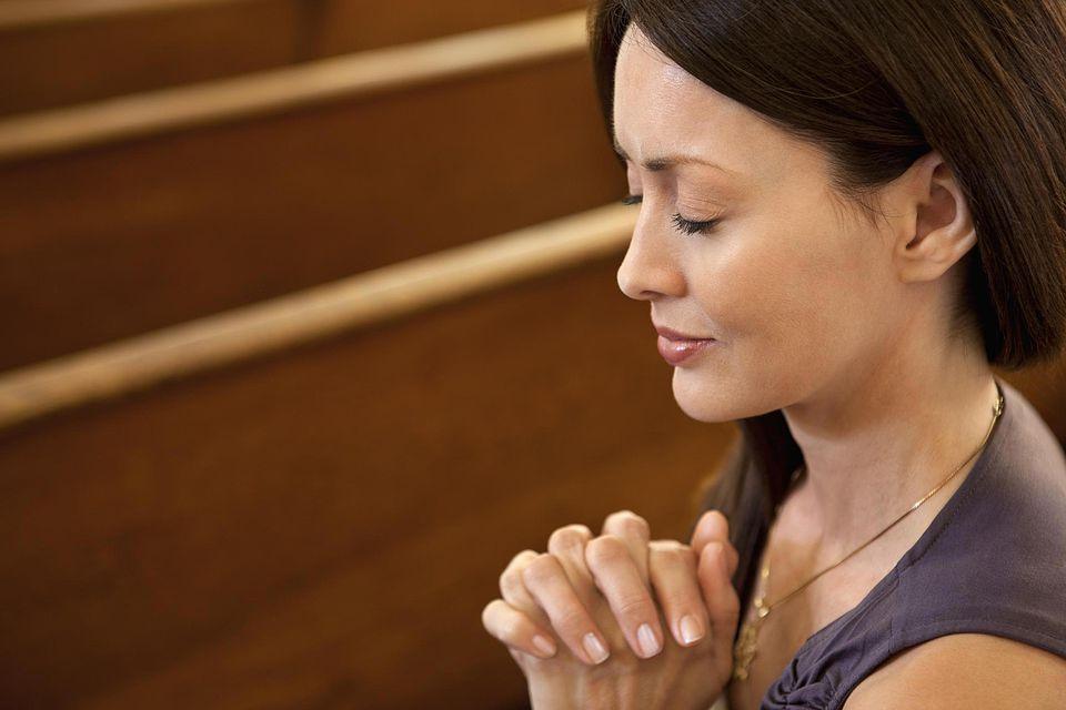 Close up of woman praying in church