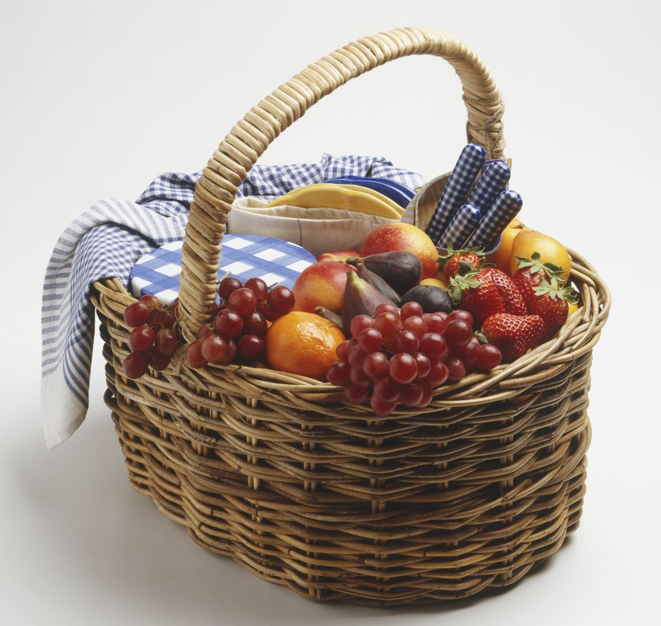 A wicker basket containing fresh fruit, cutlery, tea towel and plates