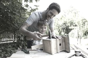 Father and son timbering a birdhouse