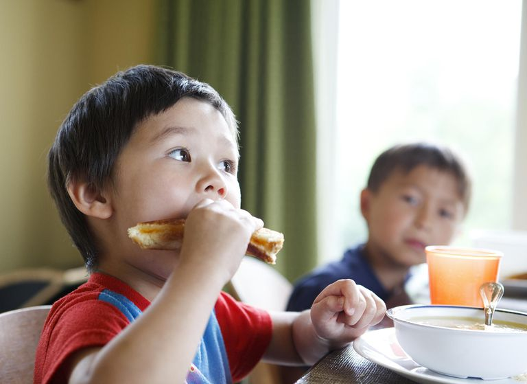 A child eating a peanut butter and jelly sandwich.