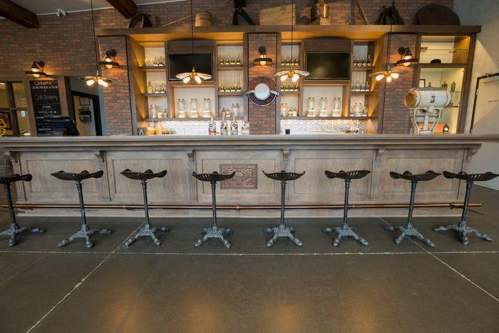 Stools lined along empty distillery bar