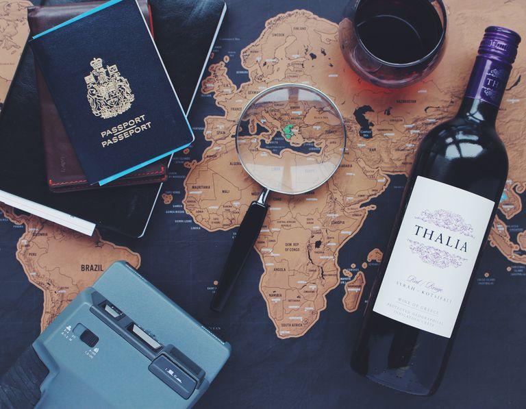 Map with wine, passport and magnifying glass