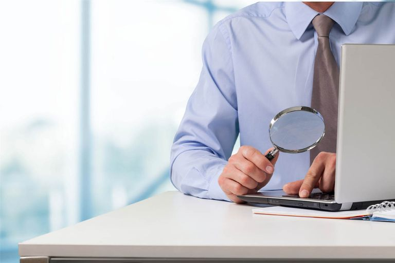 Man holding a magnifying glass over a computer