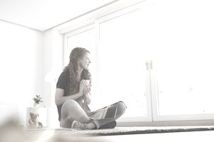 Young woman sitting on the floor of her living room looking through window