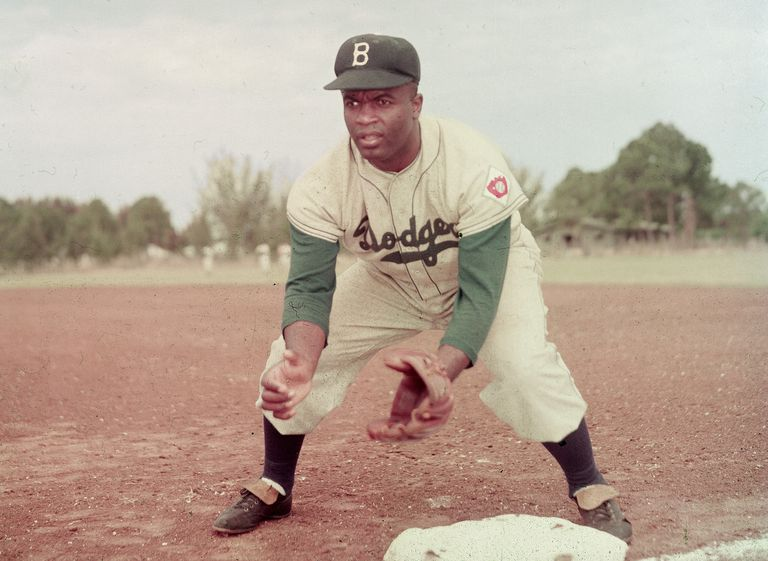 American professional baseball player Jackie Robinson (1919 - 1972) of the Brooklyn Dodgers, dressed in a road uniform, crouches by the base and prepares to catch a ball, 1951