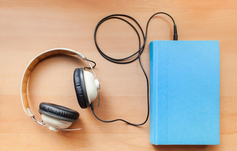 Picture of a pair of headphones plugged into a book