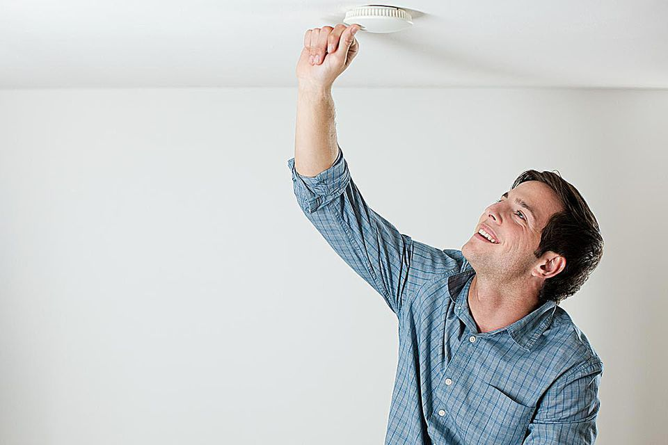 Young man testing smoke alarm on ceiling