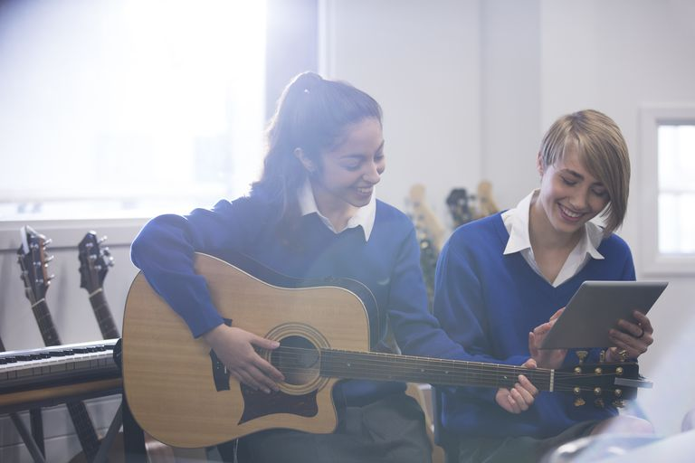 Female students playing acoustic guitar in classroom and using tablet pc