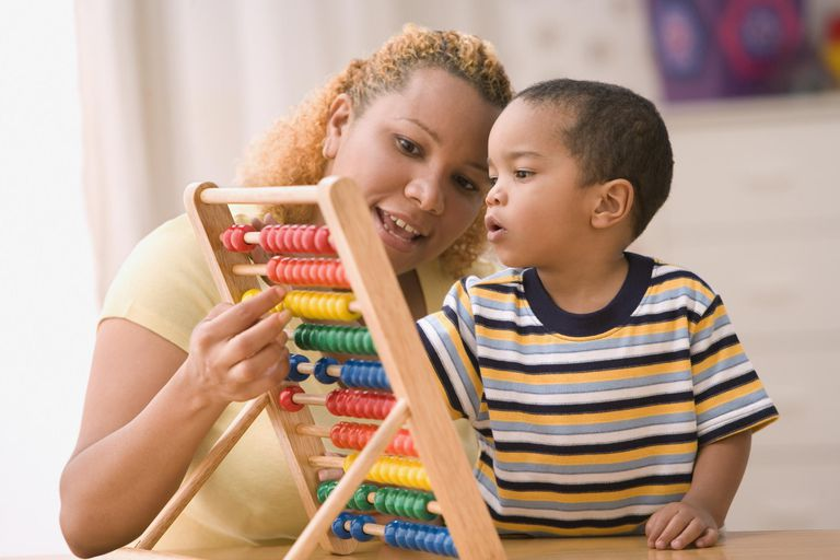 A mother teaches her son to count with an abacus.