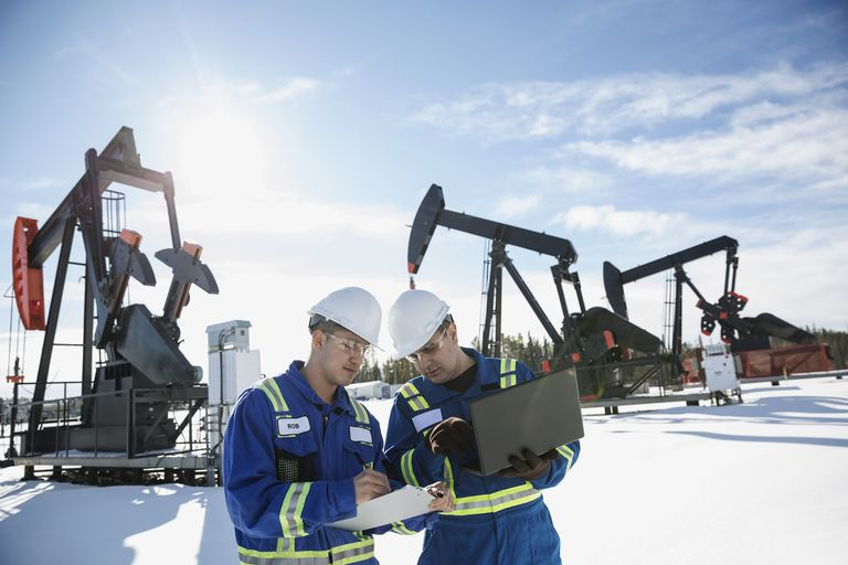 Male engineers laptop clipboard snow near drilling rigs