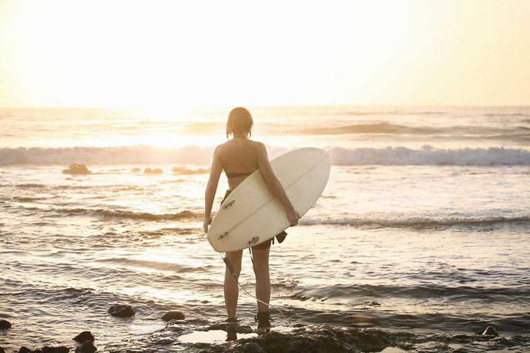 Woman with surfing board on rocky beach