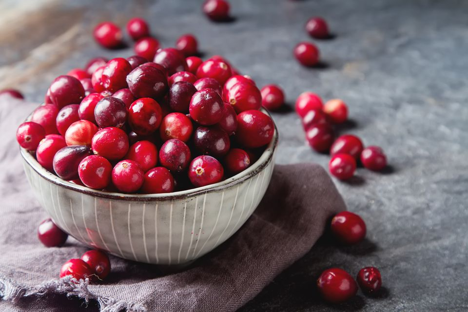 Red berries on a dark background. cranberries in a bowl.