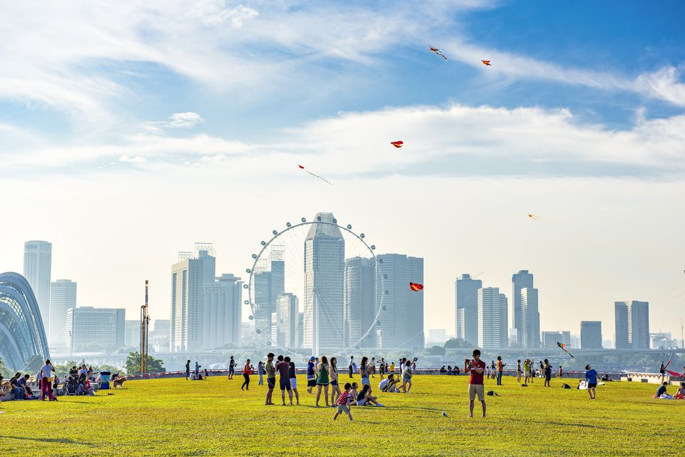 Peoples enjoy outdoor holiday activities at Singapore Marina Barrage Park with Singapore city background near Marina Bay