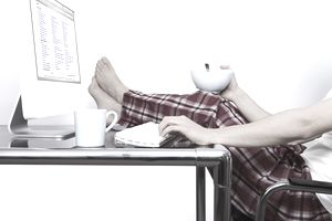Young man wearing pyjamas with feet up on desk using computer
