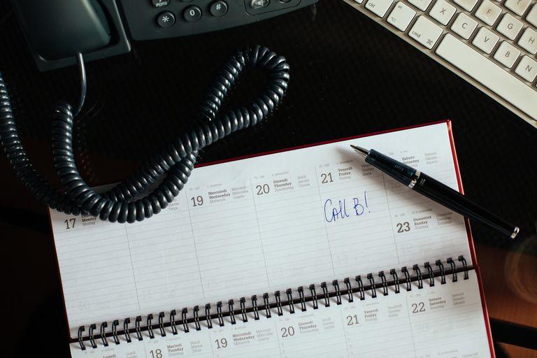 Handwritten note on agenda on glass office desk