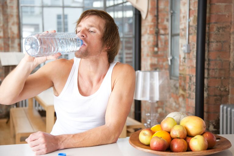 Man drinking from a large bottle of water