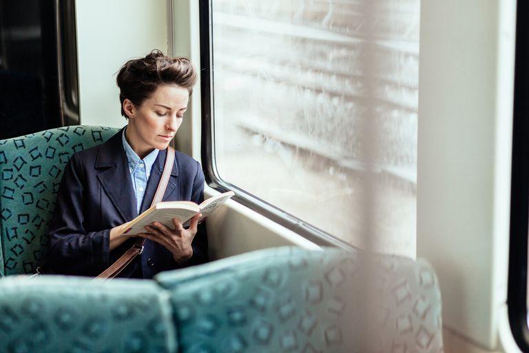 Businesswoman Reading Book In Train