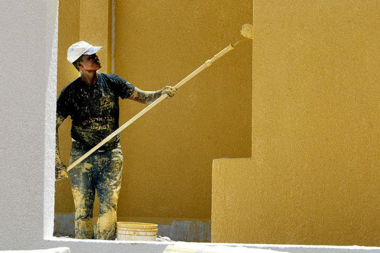 A Man Uses a Roller to Paint Walls Yellow
