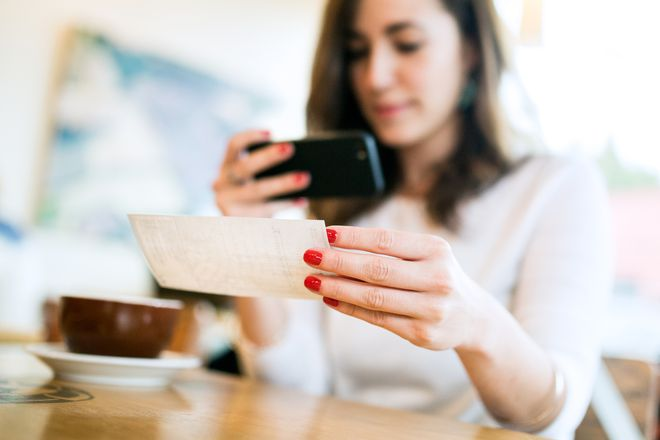 Woman depositing check to bank remotely using mobile phone