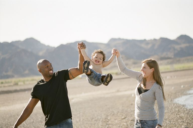 Couple walking and swinging toddler between them