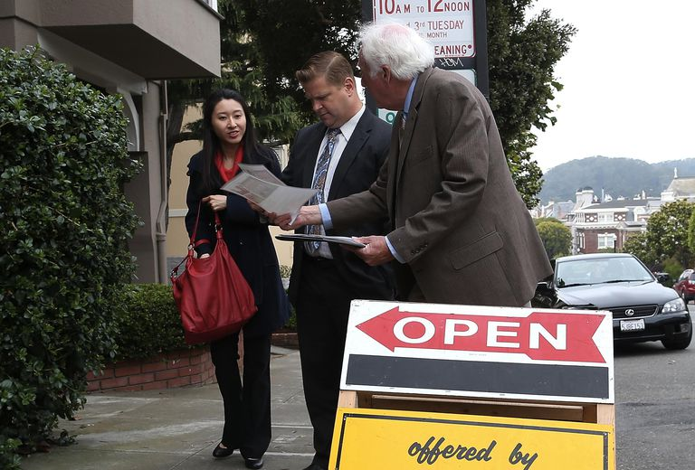 couple looking at paperwork with real estate agent on sidewalk