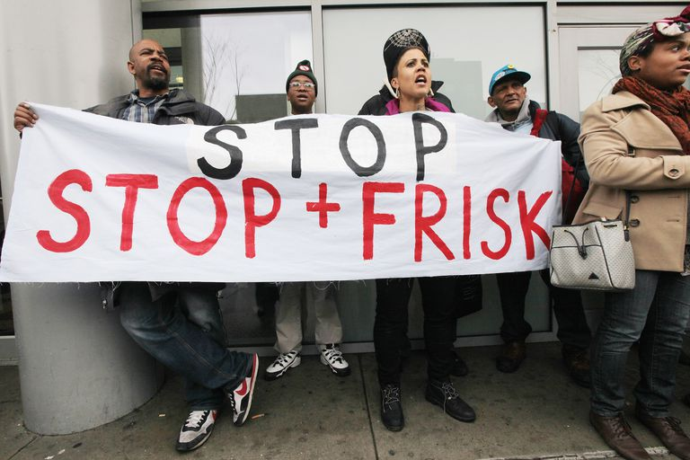 People holding sign protesting police stop and frisk searches