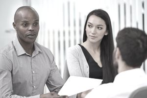 An HR manager and a manager meet with an employee to terminate his employment and hand him a dismissal letter.
