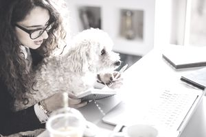 Woman taking notes with dog on lap