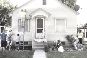 Neighbors helping paint a house.